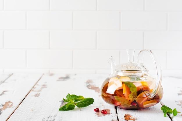 Фруктовый чай с ягодами, лимоном, лаймом и листьями мяты в стеклянном чайнике на белой светлой деревянной поверхности