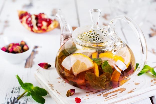 Фруктовый чай с ягодами, лимоном, лаймом и листьями мяты в стеклянном чайнике