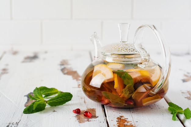 Fruit tea with berries, lemon, lime and mint leaves in glass teapot on white light wooden background. selective focus.