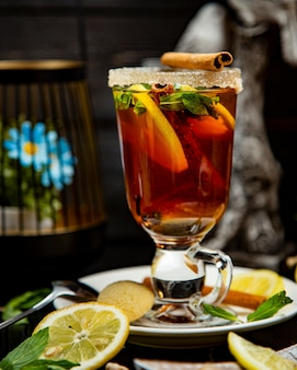 Fruit tea with lemon and cinnamon on the table