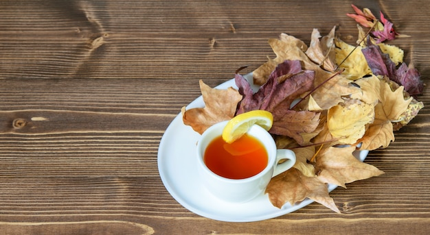 Fruit tea with lemon, heap of dry autumn leaves on the white saucer and on the wooden table.