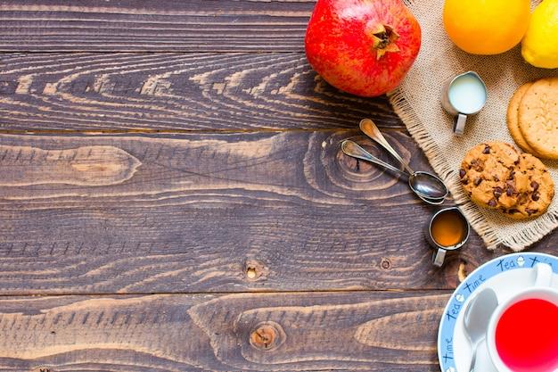 レモン、ミルク、蜂蜜、オレンジ、ザクロ、木製の背景とフルーツティー