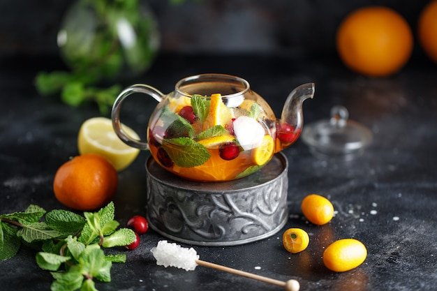 Fruit tea with mint, oranges and cranberry on dark stone background. a cup of hot tea