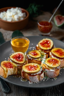 Fruit toast on toasted baguette with figs and goat cheese on a plate with honey, sesame seeds