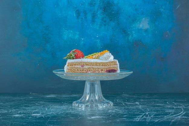 Кусок торта увенчанный фруктами на стеклянном постаменте на синем фоне. фото высокого качества