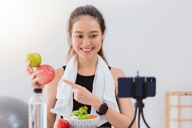 Блоггер красивой азиатской женщины здоровый показывает fruite яблока и чистую еду диеты.