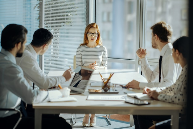 実りあるコラボレーション。魅力的な女性の上司が従業員と一緒にテーブルの先頭に座って、彼らと一緒にプロジェクト計画を作成します