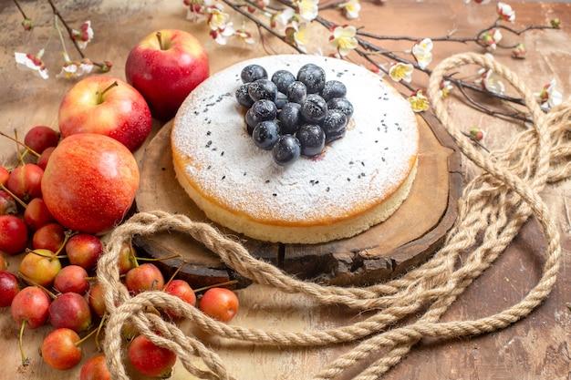 テーブルの上にブドウ3つのリンゴとベリーと果物食欲をそそるケーキ