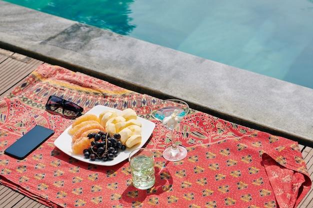 スイミングプールサイドのフルーツとカクテル