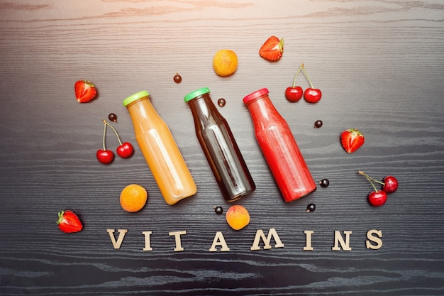 果物と黒い木製のテーブルの碑文ビタミン。食品のコンセプト