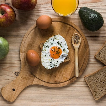 Fruits and juice near toast with fried egg
