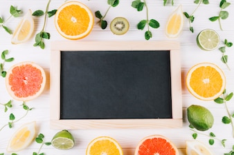Fruits and mint around chalkboard