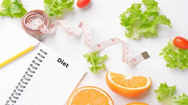Фрукты и овощи и поясная лента кладут на белый стол в виде сверху диетического и здорового