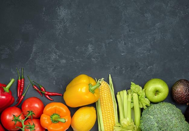 과일과 야채는 검은색 콘크리트 배경에 일렬로 놓여 있습니다 프리미엄 사진