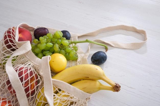 Фрукты и овощи в сетке на деревянном фоне