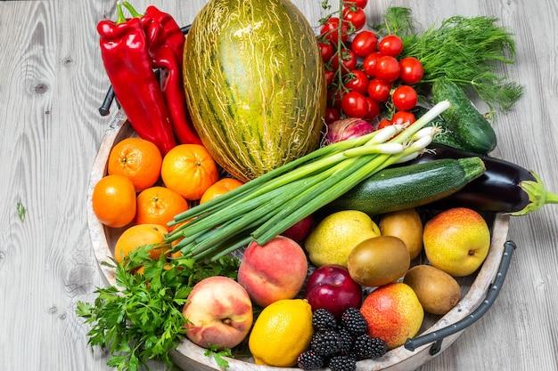 회색 나무 테이블 배경에 있는 나무 쟁반에 있는 과일과 야채