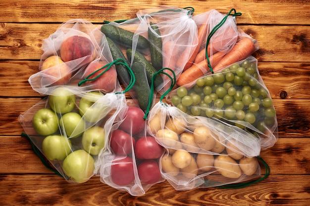 木製の背景に再利用可能な環境にやさしいバッグの果物と野菜。廃棄物ゼロ。