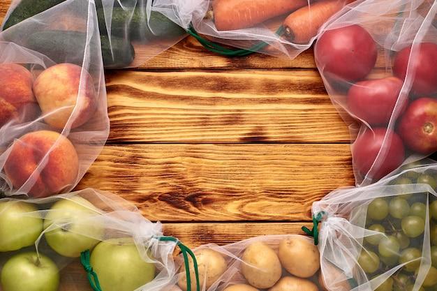 木製の背景に再利用可能な環境にやさしいバッグの果物と野菜