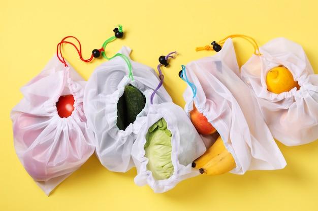 明るい黄色の表面に再利用可能な環境に優しいメッシュバッグに入った果物と野菜、ゼロウェイストコンセプト。汚染を止めなさい。上面図