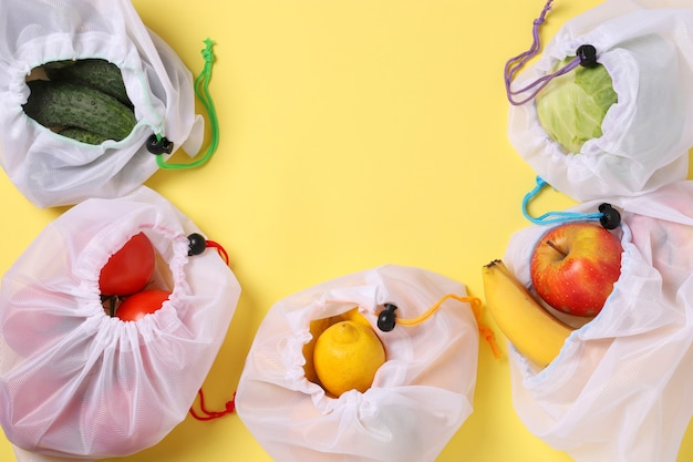 明るい黄色のテーブルに再利用可能な環境に優しいメッシュバッグに入った果物と野菜。スペースをコピーします。ゼロウェイストのコンセプト、汚染を止めます。上面図。