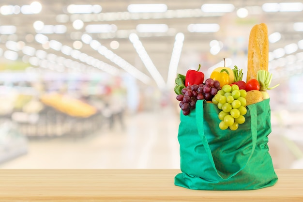 Фрукты и овощи в хозяйственной сумке на фоне супермаркета