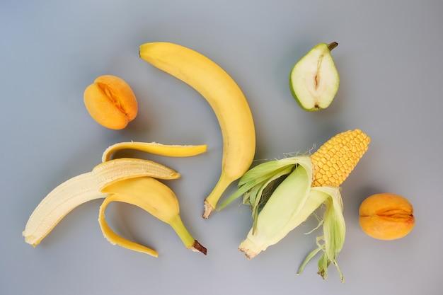 灰色の背景に果物と野菜。性教育の概念。フラットレイ。上面図。