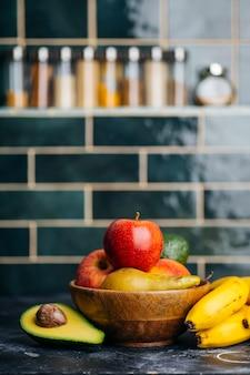果物のスムージー、ジュース、飲み物用のキッチンテーブルの果物と野菜。家庭で健康的なベジタリアン料理を調理します。健康的で健康的な食品のコンセプト