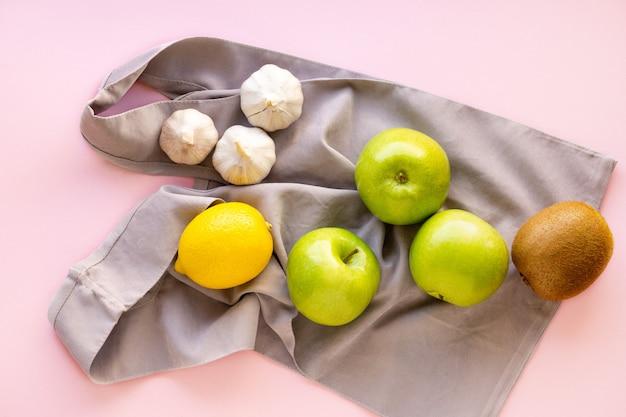 果物と野菜のピンクの背景に再利用可能な生地のバッグ