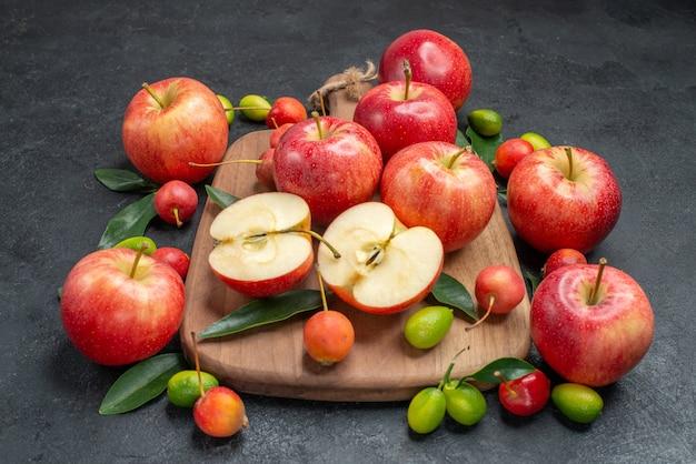 과일 옆에 보드에 잎이있는 과일 사과와 체리