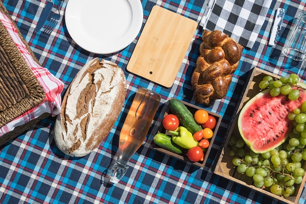 Fruits; baked bread and vegetables on checkered cloth