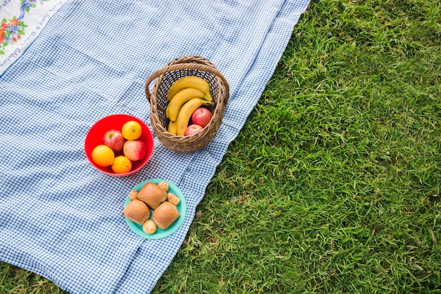 Fruits basket and baked bread on blanket over the green grass