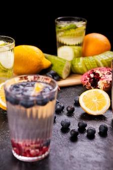 ヴィンテージの木製の背景にデトックス水とグラスの横に果物、ベリー、野菜