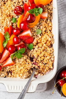 Fruits and berries oat crumble in oven dish on gray background, top view.