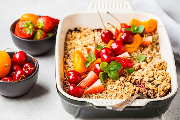 Fruits and berries oat crumble in oven dish