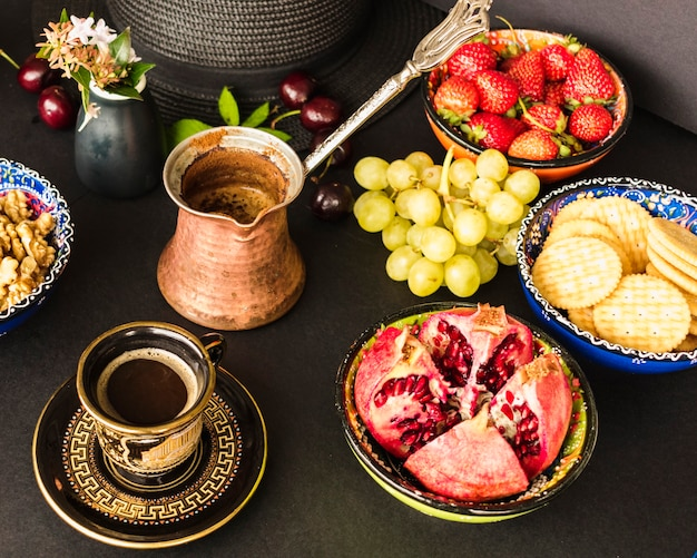 Fruits, biscuits and walnut with tea on the table
