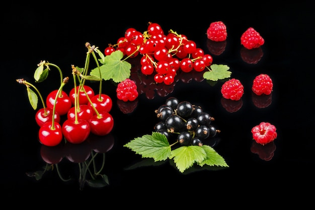 Fruits of cherry, raspberry, black currant and red currant on a dark background.