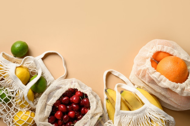 Fruits and citrics in eco-friendly mesh bags on beige background. zero waste shopping.