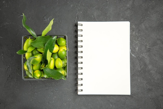 Fruits citrus fruits with green leaves in the basket white notebook