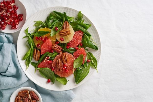 Фруктовый салат из цитрусовых с орехами, зелеными листьями салата. скопируйте пространство. сбалансированное питание. шпинат с апельсином, грейпфрутом, орехами пекан и зернами граната в миске на столе с белой скатертью.