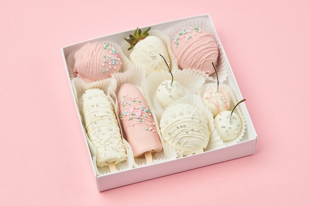 Fruits coated with white and pink chocolate are lie in a gift box