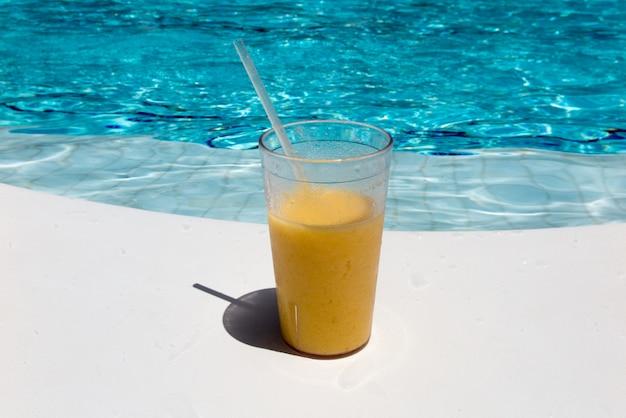 リゾートプールの端にあるフルーツカクテル。贅沢な休暇の概念。