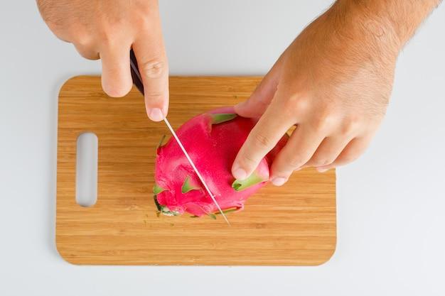 Concetto di frutta piatto disteso. mani che tagliano la frutta del drago sul bordo di legno.