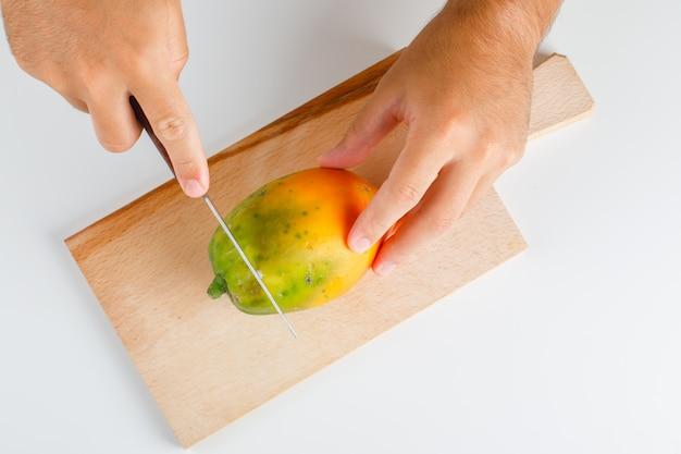 Concetto di frutta piatto disteso. mani che tagliano papaia su tavola di legno.