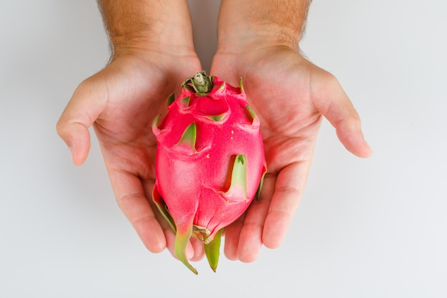Fruits concept flat lay. hands holding dragon fruit.