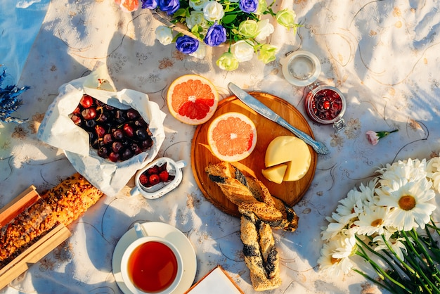Fruits, croissants, tea and flowers on tablecloth in summer sunlight. picnic concept