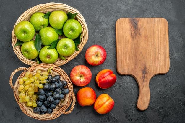 Frutta tagliere mele e grappoli d'uva nel cesto e nettarine