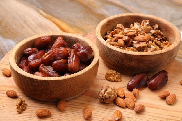テーブルの上の木製のボウルのクローズアップの果物の日付とナッツ