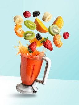 Fruits flying in a blender with fruit juice, isolated from the blue background