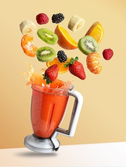 Fruits flying in a blender with fruit juice, isolated from the orange background