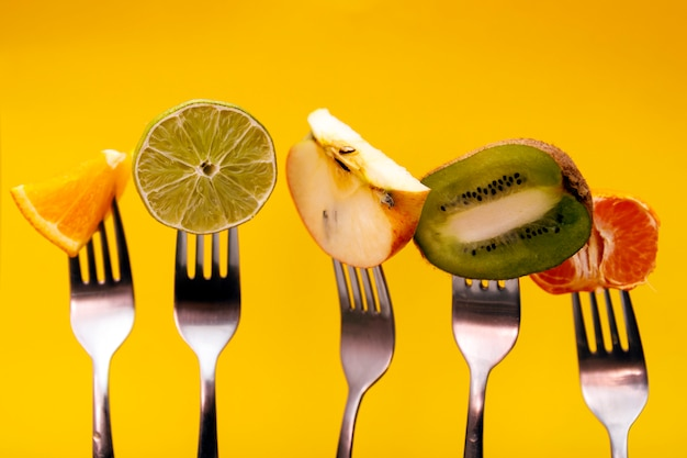 Fruits on fork isolated on yellow